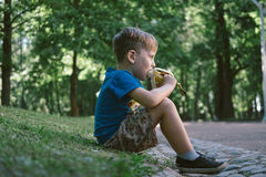 Le garçon 5 années mangent une banane en parc Photographie stock