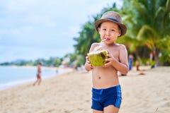 Le garçon asiatique bronzé se tient sur la plage dans un chapeau et une noix de coco de boissons photographie stock