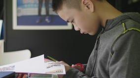Le garçon asiatique d'enfant coupant des ciseaux empaquettent à la maison clips vidéos