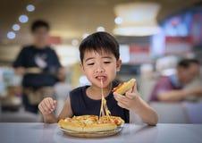 Le garçon asiatique est heureux de manger de la pizza avec une fonte chaude de fromage étirée images stock