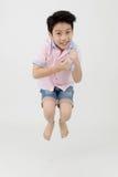 Le garçon asiatique heureux saute au studio photos stock