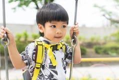 Le garçon asiatique joue sur une oscillation photos stock