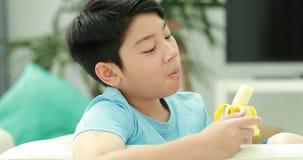 Le garçon asiatique mignon ont plaisir à manger la petite banane banque de vidéos