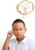 Le garçon asiatique pensant dans la salle de classe Photographie stock libre de droits