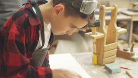 Le garçon assidu travaille avec le burin dans un magasin de menuiserie clips vidéos