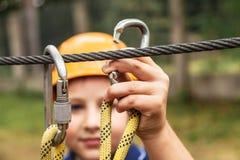 Le garçon attache la carabine pour la corde de sécurité photo stock
