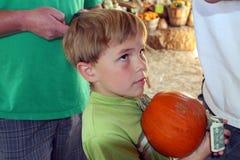 Le garçon attend dans la ligne pour acheter le potiron Images libres de droits