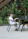 Le garçon attend un petit déjeuner à une table en plein air Images stock