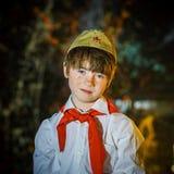 Le garçon attirant roux s'est habillé comme le pionnier soviétique avec le lien rouge Photographie stock