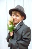 Le garçon avec des fleurs dans le jour de mère Photos stock