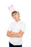 Le garçon avec des oreilles de lapin fait des visages Image libre de droits