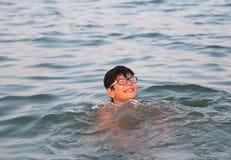 Le garçon avec des verres joue en eau de mer pendant des vacances d'été Photo stock