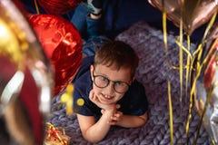 le garçon avec des verres rêve tout en se trouvant sur le lit, images libres de droits