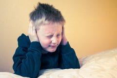 Le garçon avec des yeux a fermé des oreilles de bâche avec des mains photographie stock libre de droits