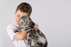 Le garçon avec l'écossais plient le chat d'isolement sur le fond blanc Amitié d'animal familier d'enfant Photographie stock libre de droits