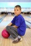 Le garçon avec la bille s'assied sur l'étage dans le bowling Image libre de droits