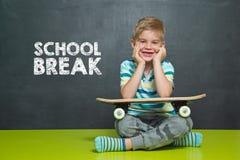 Le garçon avec la planche à roulettes et le conseil pédagogique avec l'ÉCOLE des textes SE CASSENT Photos stock