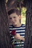 Le garçon avec la rose le concept de l'amour des enfants Photographie stock