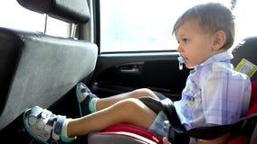 Le garçon avec le mamelon monte le siège de voiture banque de vidéos