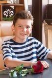 Le garçon avec s'est levé à une table en café de rue Images libres de droits