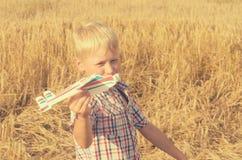 Le garçon avec sa main court le modèle de l'avion dans le ciel Photos libres de droits