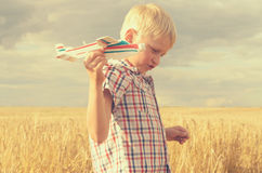 Le garçon avec sa main court le modèle de l'avion dans le ciel Photo stock