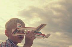 Le garçon avec sa main court le modèle de l'avion dans le ciel Photos stock