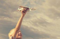 Le garçon avec sa main court le modèle de l'avion dans le ciel Photographie stock