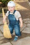 Le garçon avec un balai photo stock