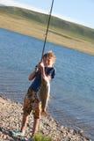 Le garçon avec un grayling de rotation de loquet photos libres de droits