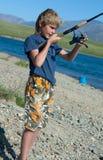 Le garçon avec un grayling de rotation de loquet images libres de droits
