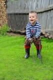 Le garçon avec un marteau de fer pour conduire une tige en métal photos libres de droits