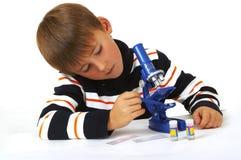 Le garçon avec un microscope Photo stock