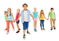 Le garçon beau avec beaucoup d'amis tiennent des mains ensemble Image stock