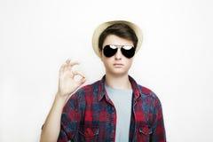 le garçon beau avec les lunettes et le chapeau et les expositions approuvent le signe Photographie stock