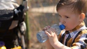 Le garçon beau boit l'eau claire d'une bouteille un jour ensoleillé dehors banque de vidéos