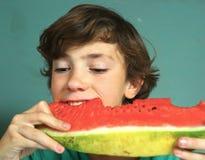Le garçon beau de la préadolescence mangent la pastèque Photographie stock