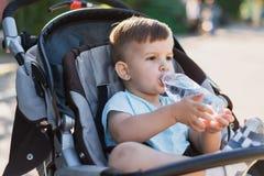 Le garçon beau s'assied dans une poussette et boit l'eau d'une bouteille un jour chaud d'été image libre de droits