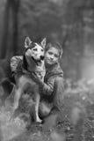 Le garçon blanc noir et le sien de photo poursuivent le chien de traîneau sur le fond des feuilles au printemps Photographie stock libre de droits