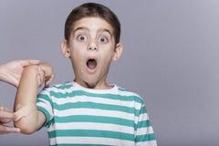 Le garçon blessé avec un coude meurtri réagit en douleur Photographie stock libre de droits