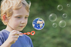Le garçon blond caucasien joue avec des bulles de savon image stock
