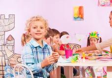 Le garçon blond dans la classe préscolaire s'asseyent par la table Photos libres de droits
