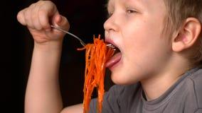 Le garçon blond drôle mange de la salade coréenne de carotte dans la cuisine à côté de son frère Les enfants sont heureux ensembl banque de vidéos
