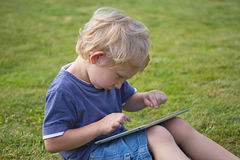 Le garçon blond joue avec le comprimé de PC dehors photo stock