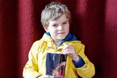 Le garçon blond mignon de petit enfant mangeant du maïs éclaté au cinéma avant le film commence Photographie stock
