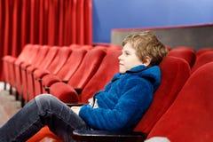 Le garçon blond mignon de petit enfant mangeant du maïs éclaté au cinéma avant le film commence Image libre de droits