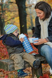 Le garçon boit du thé d'un thermos avec sa mère Photo stock