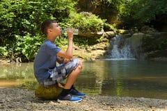 Le garçon boit l'eau de la bouteille se reposant sur la pierre photographie stock libre de droits
