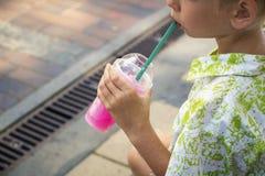 Le garçon boit la glace rasée par bonbon images stock