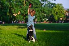 Le garçon bouclé de 8-9 ans joue avec le chien Images stock